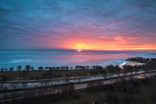 A Beautiful Sunrise Landscape Photograph Of The Bright Orange And Yellow Sun Peering Over The Horizon On Lake Michigan In Chicago With Pink And Blue Clouds In The Sky And Cars On Lake Shore Drive.