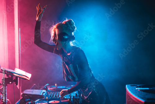 happy dj girl with blonde hair using dj mixer in nightclub with smoke Wallpaper Mural