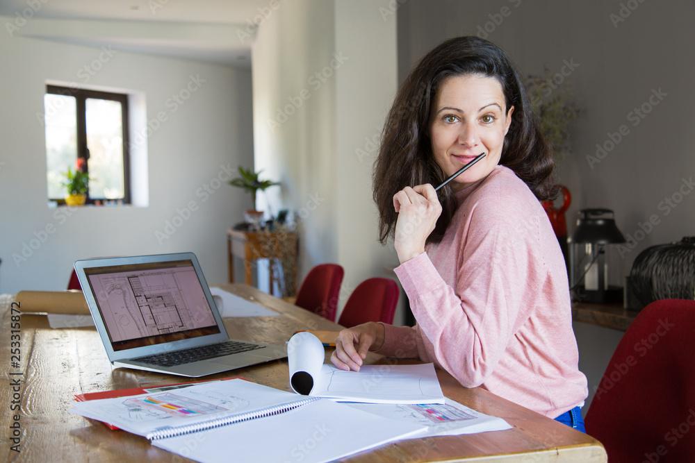 Fototapeta Cheerful apartment designer at her workplace