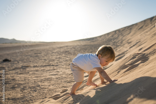Handsome baby boy climbing on a sand dune. Fototapeta