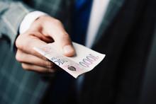 Businessman Giving A 1000 Czech Korunas Banknote.