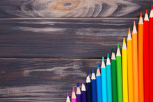 Many Different Colored Pencils On Brown Wooden Background