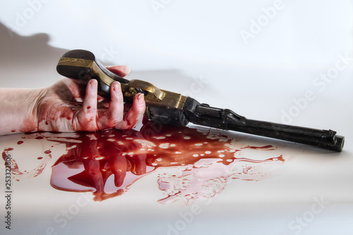 A blood covered hand holds a vintage gun on a white background.  Blood splatter can be seen.  Position of the hand suggests the person is dead.