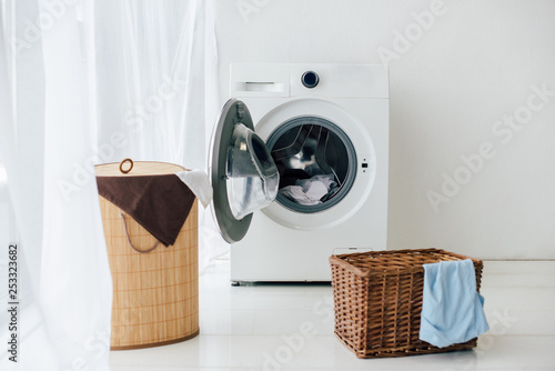 Obraz opened washer and brown baskets in laundry room - fototapety do salonu