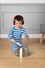 Little Boy Wearing Headphones Playing Drums With Pots And Pans