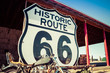 canvas print picture - A large Route 66 road sign with a weathered motorcycle in the foreground.