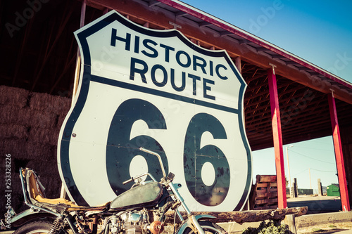 Photo  A large Route 66 road sign with a weathered motorcycle in the foreground