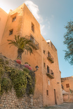 Low Angle View Of Ocher Color Buildings Against Blue Sky At The Old Town Of Ibiza, Spain. Travel, Mediterranean And Vacation Concept.