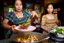 Thai Mother And Daughter Plating Freshly Cooked Red Curry In Rustic Traditional Kitchen