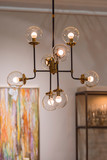 Modern brass chandelier. Pendant lamp with round glass shades and gold-colored copper tubes