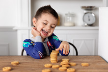 Smiling Boy Playing With Biscuits While Sitting At Home