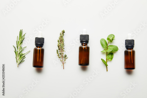 Canvas Prints Condiments Flat lay with herbs and bottles with essential oil on white background