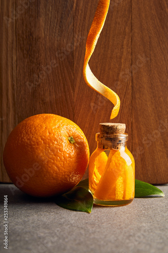 Orange and organic essential oil in glass bottle on wooden background
