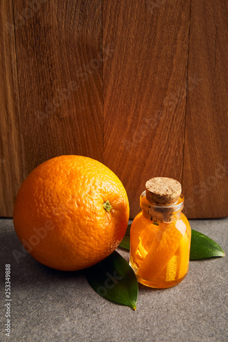 Whole orange with glass bottle of essential oil on dark surface