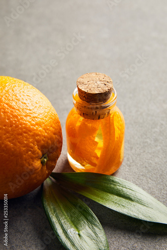 Ripe orange with glass bottle of essential oil on dark surface