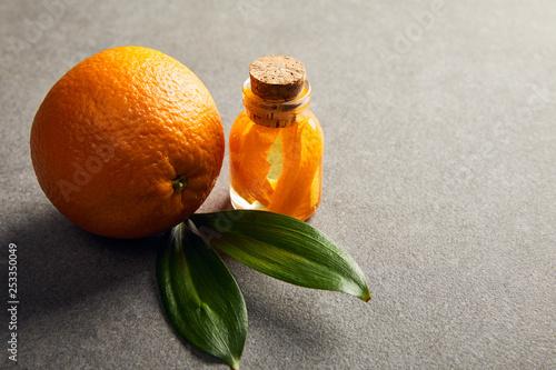 Fresh whole orange with essential oil on dark surface