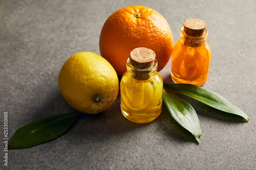 Bottles of essential oil with lemon and orange on dark surface