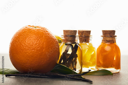 Bottles of essential oil with orange and vanilla on white background