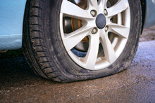 Flat Tire Of Blue Car On The Road Waiting For Repair.  Car Tire Leak Because Of Nail Pounding. .
