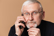 Old thoughtful man with gray hair and beard in eyeglasses and sweater amazedly looking in camera while talking on cellphone over beige background