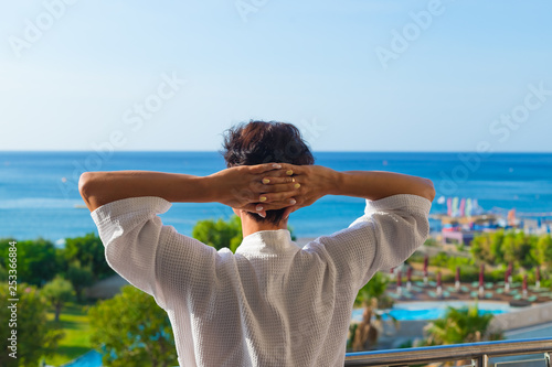 Relaxed young woman in white cozy bathrobe standing on balcony in summer morning. brunette girl on summer vacation.Woman in bath robe looking at beautiful ocean view from a tropical balcony,patio