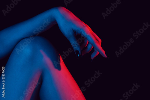female hand on knee close up with neon light
