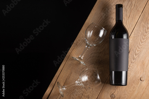 Fotografie, Obraz  A bottle of red expensive wine with a black blank label on a dark background with a glass