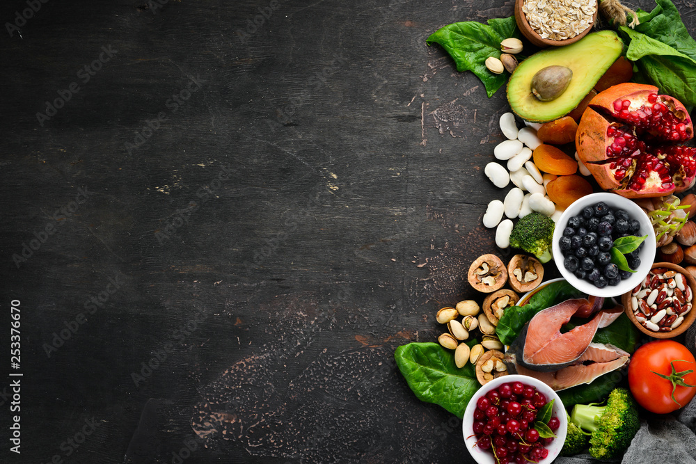 Fototapeta Healthy food: Fish, blueberries, nuts, pomegranate, avocados, tomatoes, spinach, flax. Concept of Dietary Nutrition. Top view.