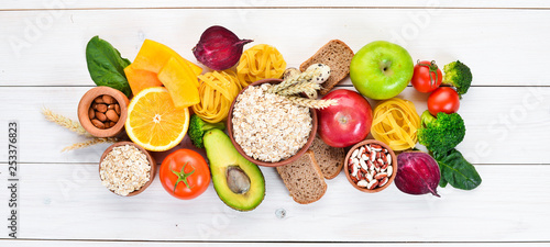 Fotomural Healthy food containing carbohydrates: bread, pasta, avocados, flour, pumpkin, broccoli, beans, spinach
