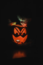Boy Looking At Jack O Lantern In Darkroom During Halloween