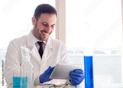 Fotografía  Biologist analyzing tests on tablet in laboratory