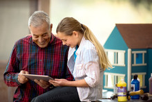 Happy Senior Man And His Young Granddaughter Looking At A Digital Tablet.