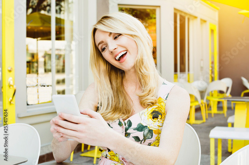 Fotografie, Obraz  Front view of a young blond girl looking at her phone and laughing while outdoor