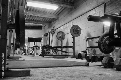 Valokuva  Black and white photo of a dirty, grungy ,hard core, weight room ,gym