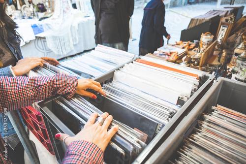 Tuinposter Muziekwinkel girl choosing discs in cosmopolitan city street market