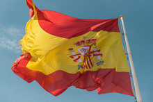 Flag Of Spain Beautiful And Big To The Background Palms And Blue Sky With Some Clouds.