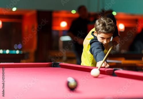 Cute boy in yellow t shirt plays billiard or pool in club