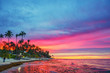 canvas print picture - Vibrant sunset over tropical beach and palm trees in Dominican republic