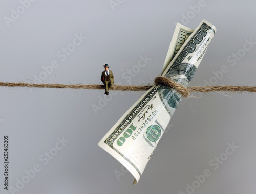 Photo  A miniature man sitting next to a $100 bill hanging from a rope.