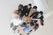 Male and female businessmen join hands in the hall of office.Top view.