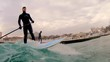 Winter surfing. action 4k shot from the water of young male surfer surfing in ocean