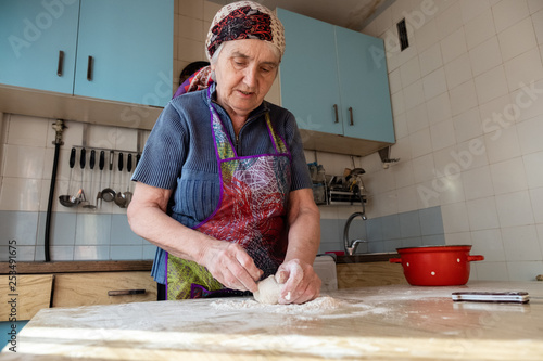 Senior woman kneading the dough in her home kitchen, grandmother cooking bakery Fototapeta