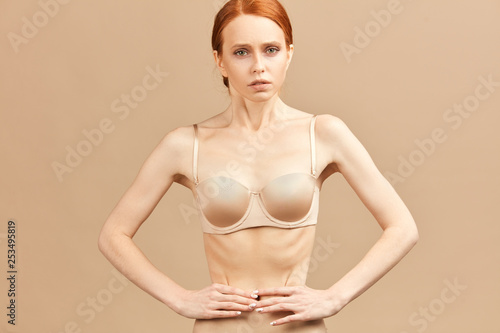 Skinny suffering female in nude underwear tied her waist with measuring tape pos Wallpaper Mural
