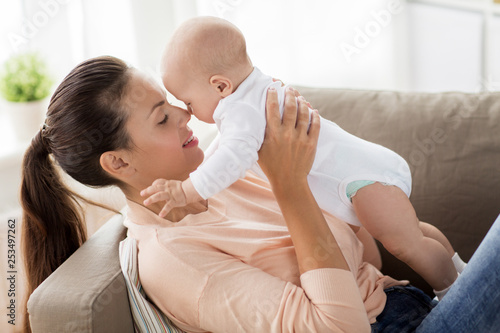 Photo sur Toile Kiev family, motherhood and people concept - happy mother with little baby boy lying on sofa at home