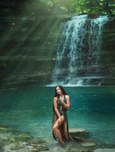 Magic Tropical Nature, Dark-haired Sexy Girl Comes Out Of The Azure Transparent Clear Waterfall Lake Water, Sea Nymph In Green Dress With Deep Neckline. Mermaid In The Sun Rays. Art Photography