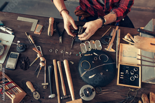 guy is sitting at messy desk in the workshop, top view cropped photo Fotobehang