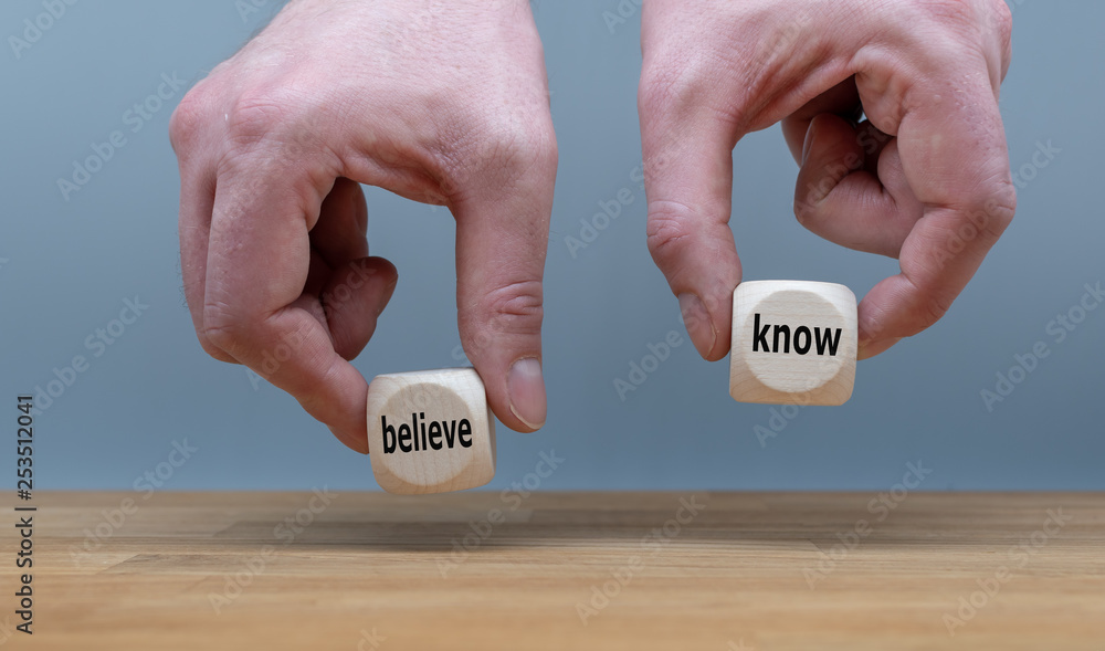 Fototapeta Conflict of knowing or believing. Two Hands hold two dice with the words