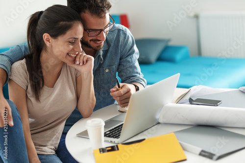 Fototapeta Husband and wife sitting at home and buying online stocks actions. obraz