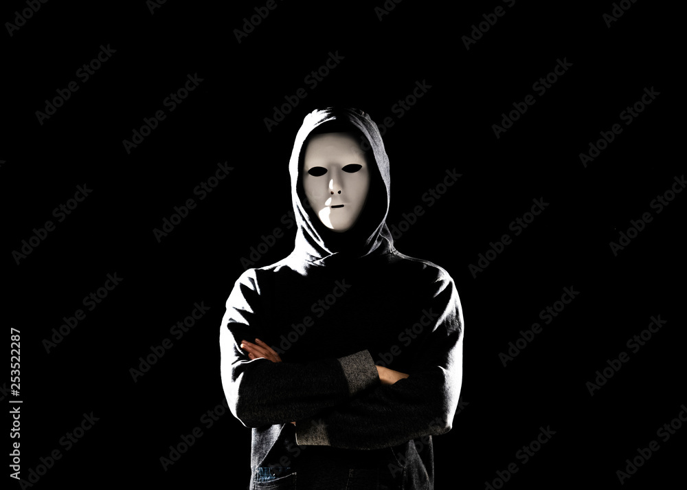 Fototapeta Computer hacker in white mask and hoodie. Obscured dark face. Data thief, internet fraud, darknet and cyber security concept.