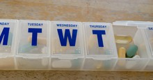 Close Up On A Medical Prescription Pill Box Organizer Full Of Vitamins And Health Supplements With A Glass Of Water.